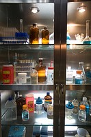 Test tubes, vials and bottles being stored in lit cabinet in a research laboratory.