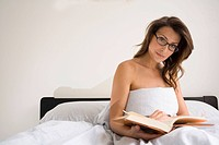 brunette woman in bed reading with glasses.She is sitting up with bed sheet wrapped around her breasts.Daylight lighting, nuetral background,She is lo...