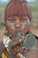 Young hamer girl blows a horn to attract men during the jumping of the bull ceremony Ethiopia Africa
