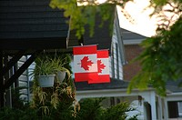Two Canadian flags hanging in front of a house