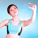 Young woman in exercising outfit holding out arm
