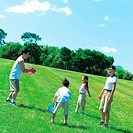 Children 7_9 playing flying disc with parents at park
