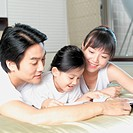 Parents accompany their daughter in reading