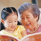 An elderly woman reading to her granddaughter