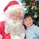 Boy sitting with Santa Claus, portrait