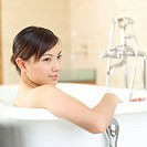 Close_up of young woman resting in bathtub, looking away, smiling