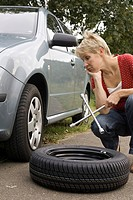 Woman trying to change tyres