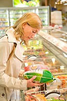 Woman comparing frozen poultry in the supermarket