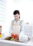 Young woman washing tomatoes in kitchen sink, smiling