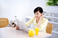 Young woman reading newspaper at table, Wire Fox Terrier sitting next