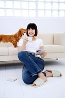 Young woman sitting on floor holding cup and book, Dachshund licking her face on sofa behind