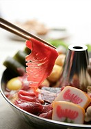 Slice of raw meat hanging on chopsticks above a Chinese hot pot