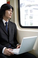 Businessman looking out of window on train with laptop on thigh