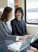 Businessman and businesswoman sitting on train with laptops on thighs, talking
