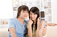One person photographing young couple, smiling, portrait