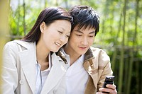 Young couple looking at mobile phone outdoors, smiling