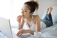 One young woman lying on bed eating and looking at laptop, portrait