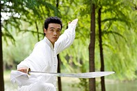 Young man in martial arts pose in park
