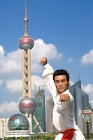China, Shanghai, Pudong, Business District, skyline, young man doing martial arts on the Bund