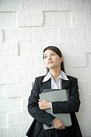 Young businesswoman with folders standing by wall, close_up