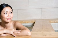 Young woman bathing in tub