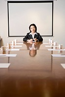 Businesswoman at head of table in boardroom, portrait