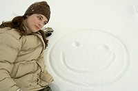 Teenage girl lying in snow beside drawing of smiley face, close_up