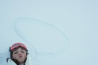 Teenage girl lying on the ground next to word bubble drawn in snow, looking at camera
