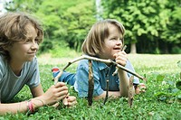 Two girls lying on grass, holding sticks, smiling, one with Down´s Syndrome