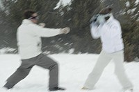 Young couple playing in snow, side view, blurred motion