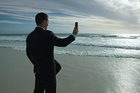 Businessman standing on beach, photographing sea with photophone