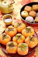 Teapot, a cup of tea, moon cakes and a tray of persimmons