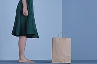 Female standing beside paper shopping bag, side view, cropped