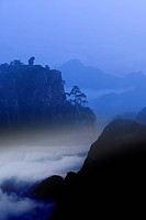 Monkey standing on a peak, gazing downwards, Mt Huangshan, digitally enhanced