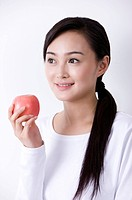 Young woman holding an apple, smiling