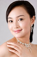 Young woman wearing jewelry, smiling, close_up