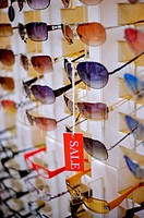 Red ´Sale´ sign hanging from a pair of sunglasses, among rows of sunglasses, close_up