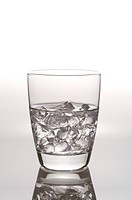 Glass of water with ice cubes, still life