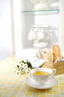 A cup of tea, flowers and a basket of bread on the table