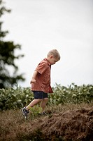 Boy running uphill in field, Ontario