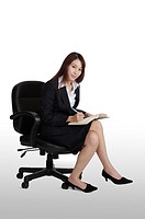 Young business woman sitting on the chair and looking at the camera