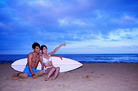 Young man and young woman sitting on beach with surfboard and looking away