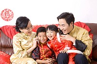 A family in traditional clothes sitting on the sofa and smiling happily