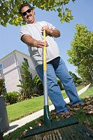Portrait of man raking lawn in garden
