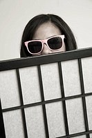 Young woman, wearing sunglasses, looking over the top of a screen.