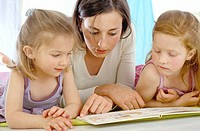 Woman and two little girls looking at book