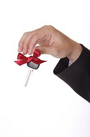 One hand holding a key with bowknot