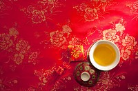 A cup of tea and Chinese decoration on red textile