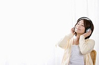 Young woman listening to music with eyes closed
