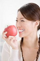 Young woman holding a red apple and smiling happily, portrait